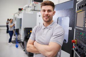 Man standing by a CNC machine