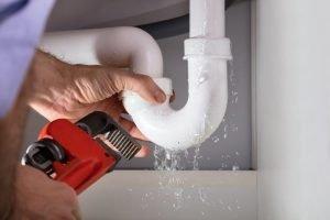 Plumber fixing a water leak.